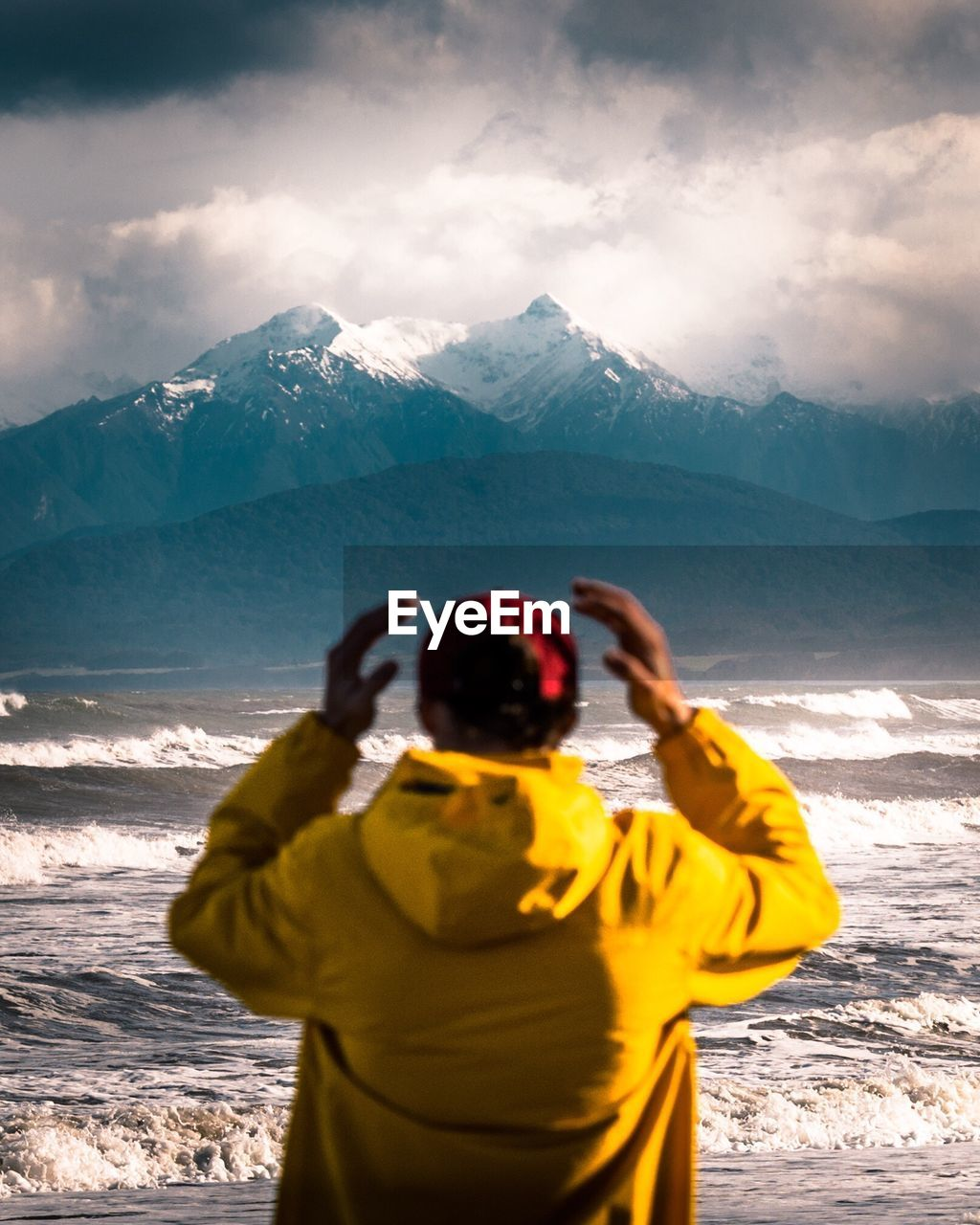 Rear View Of Young Man Standing At Beach Against Snowcapped Mountains