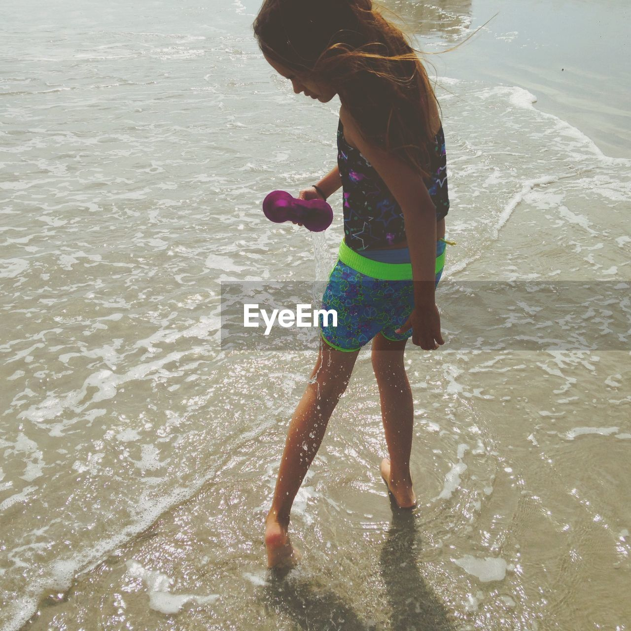 full length, water, beach, girls, childhood, leisure activity, real people, one person, wet, motion, ankle deep in water, fun, vacations, sand, elementary age, outdoors, day, summer, nature, lifestyles, sea, playing, sand pail and shovel, people