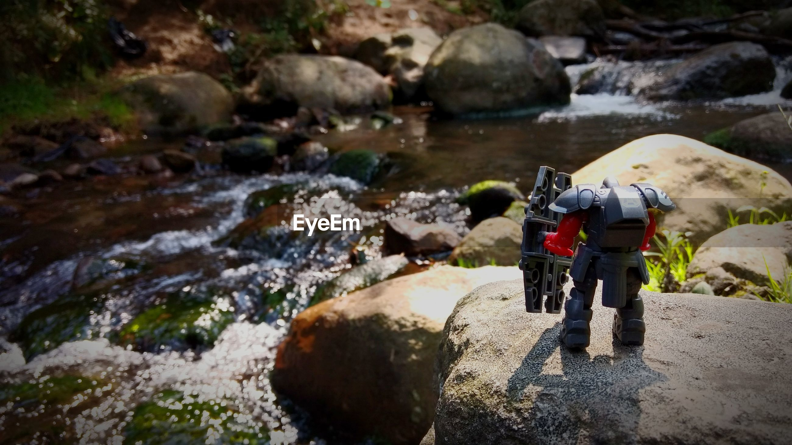 Close-up of robot toy on rock against stream
