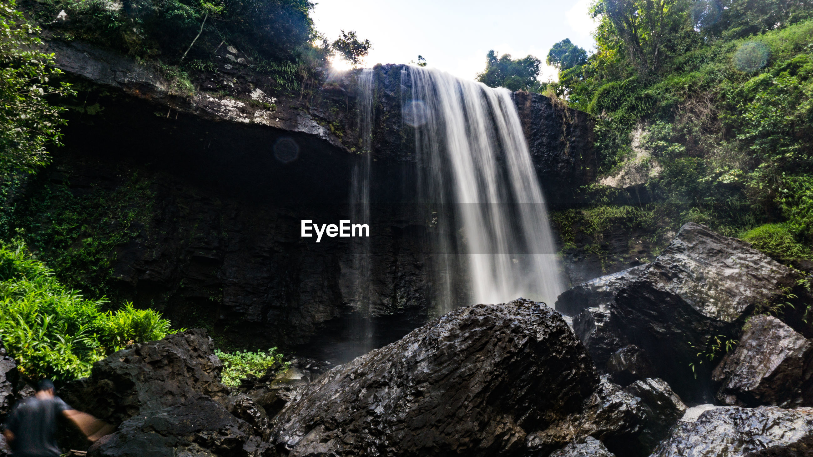 LOW ANGLE VIEW OF WATERFALL IN FOREST AGAINST SKY