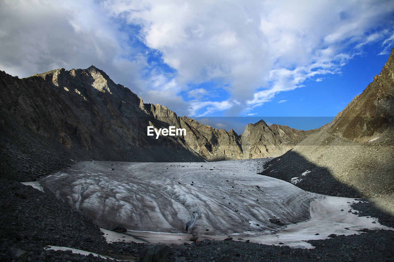 Glacier in an alpine rocky gorge against the background of the sky with clouds