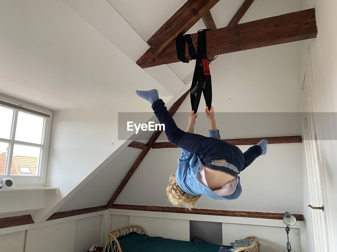 Low angle view of boy hanging at home