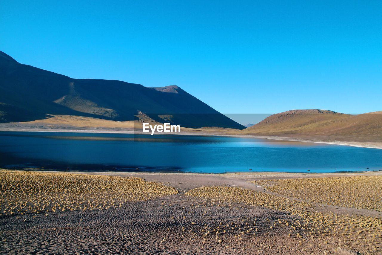 sky, scenics - nature, tranquil scene, beauty in nature, tranquility, blue, mountain, land, clear sky, water, no people, nature, non-urban scene, sand, copy space, day, environment, landscape, desert, climate, arid climate, outdoors, salt flat