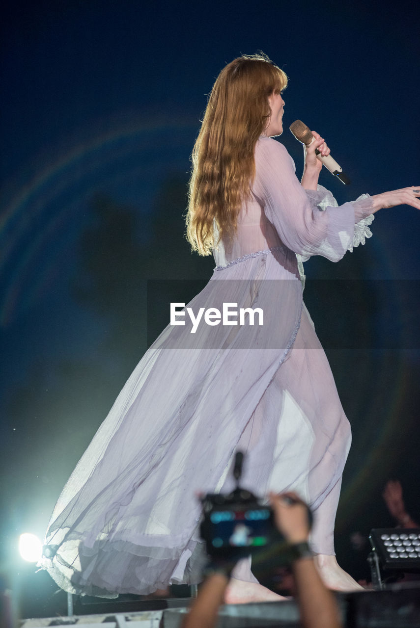 REAR VIEW OF WOMAN STANDING ON STAGE