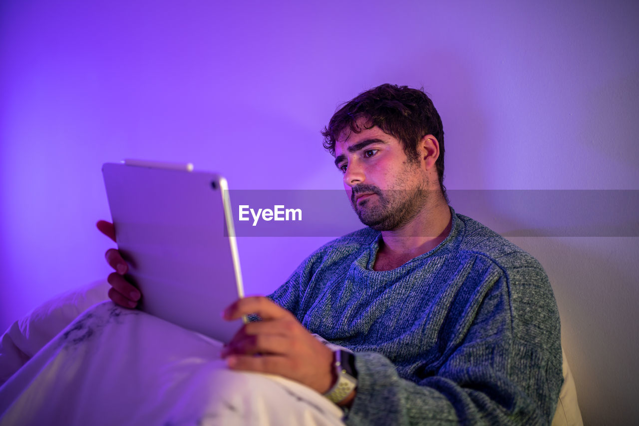 Man looking at digital tablet while sitting on bed against wall