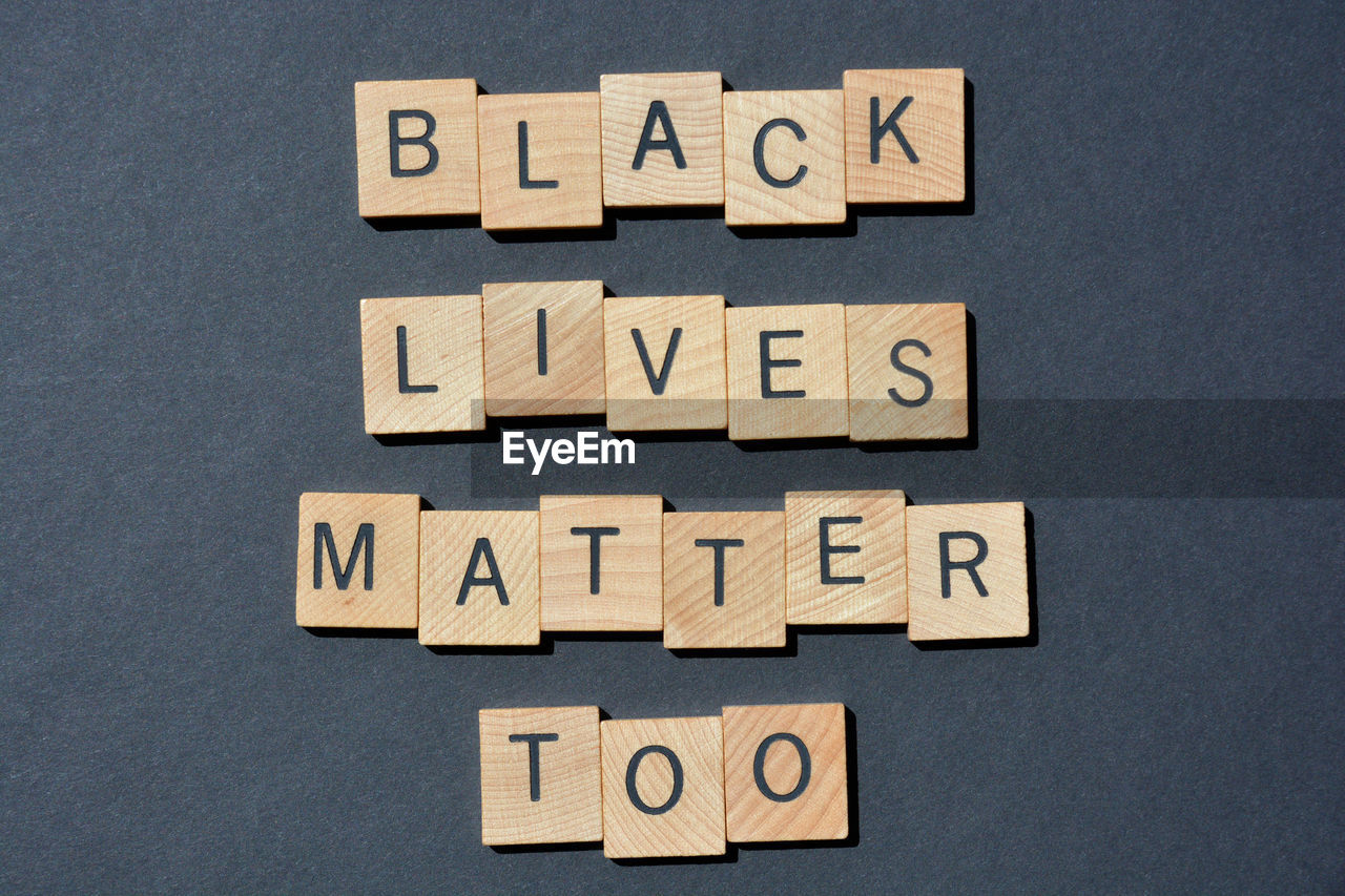Black lives matter too, words in 3d wooden alphabet letters isolated on black background