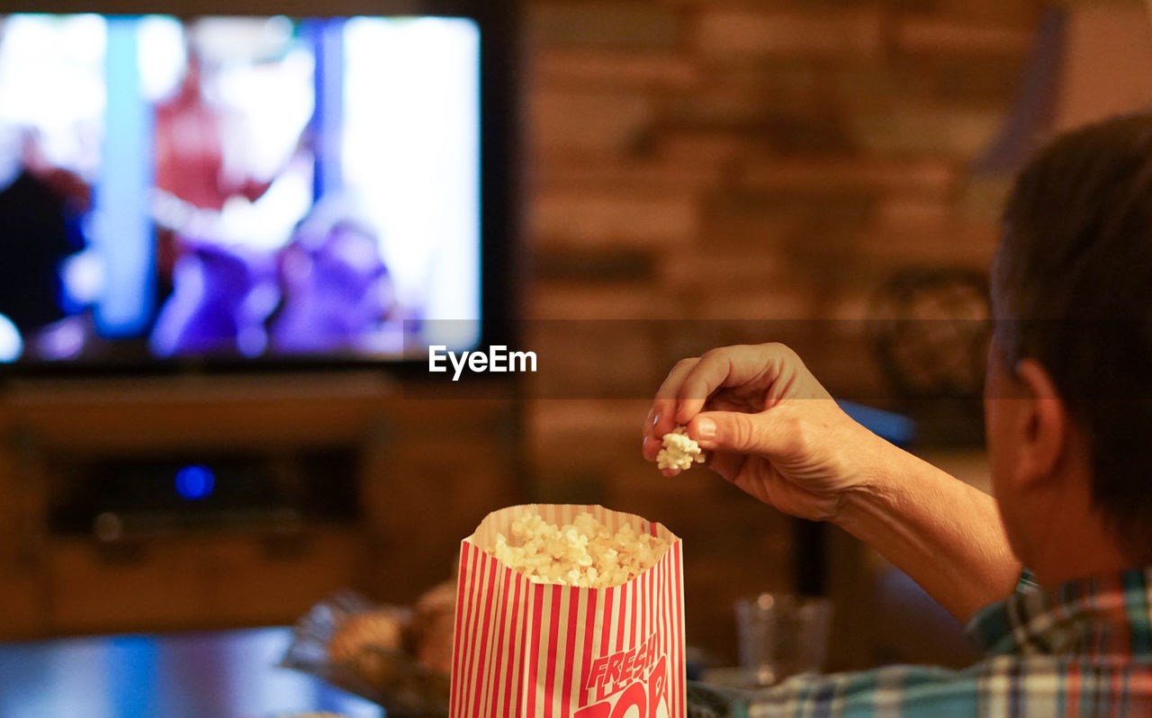 Rear view of man eating popcorn while watching tv on sofa at home