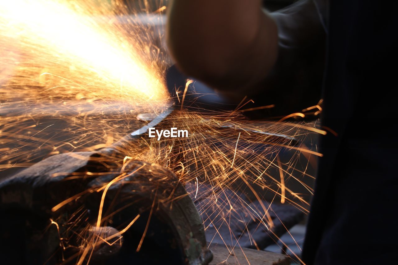 motion, blurred motion, real people, one person, heat - temperature, sparks, working, long exposure, human body part, occupation, human hand, industry, burning, men, hand, metal, holding, fire - natural phenomenon, fire, metal industry, skill, finger, welding