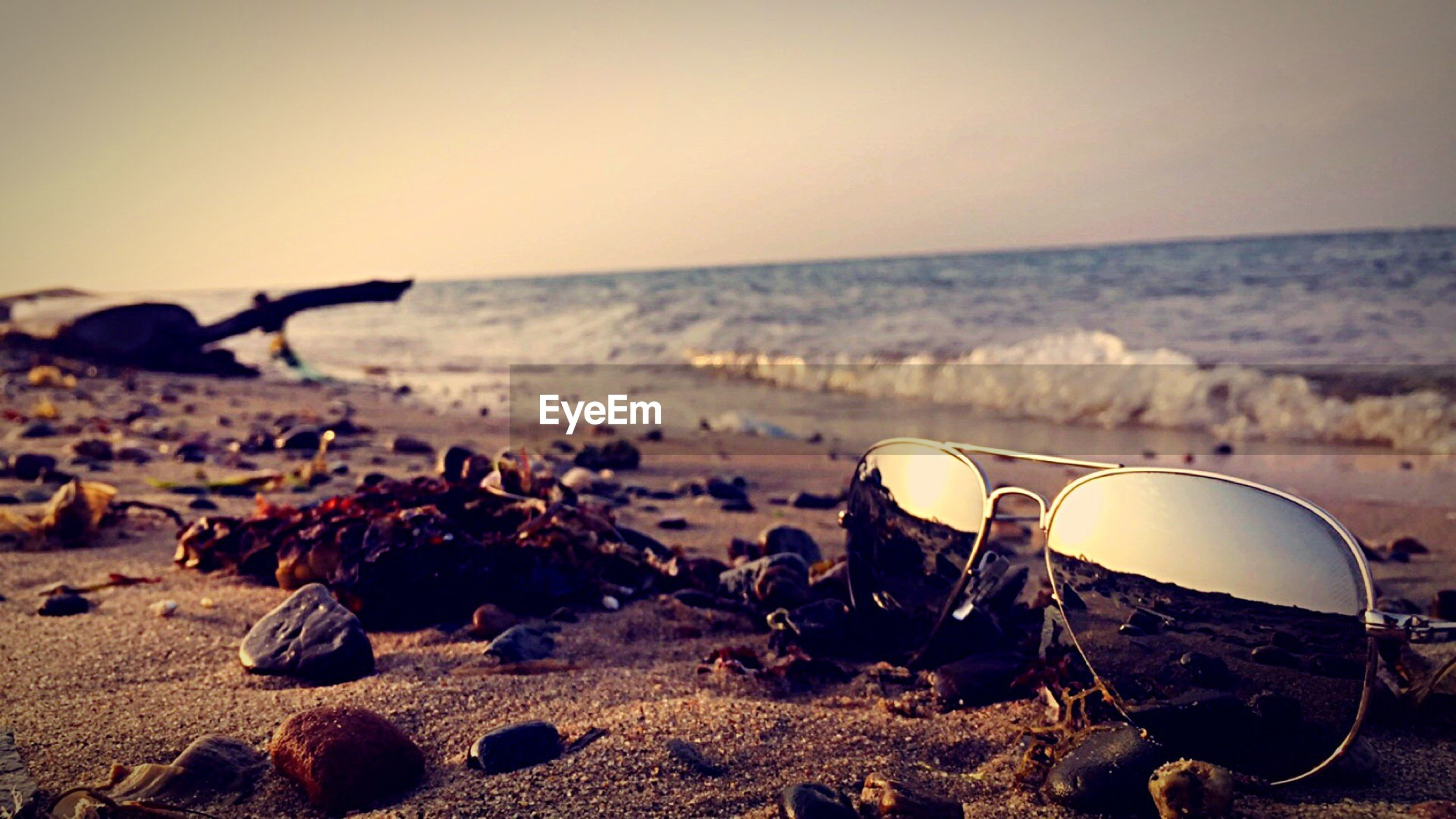 Surface level of sunglasses on sea shore against clear sky during sunset