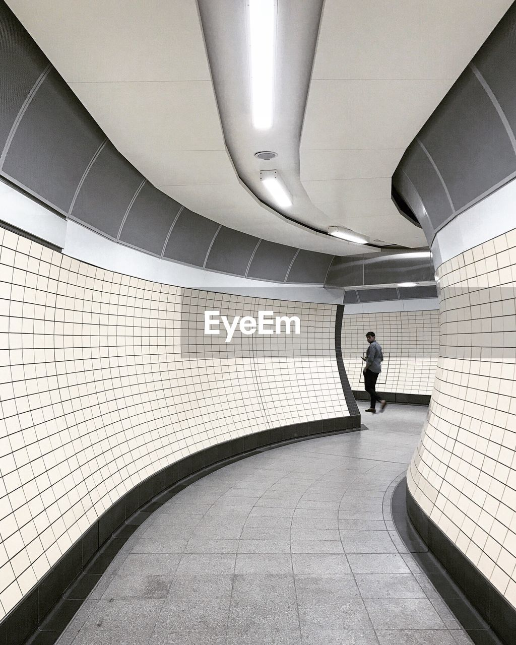 Rear View Of Man Walking In Corridor