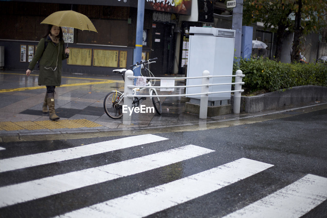 WOMAN ON ZEBRA CROSSING AT CITY