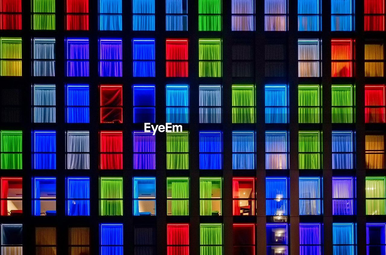 multi colored, no people, full frame, built structure, architecture, glass - material, pattern, backgrounds, building exterior, stained glass, illuminated, design, building, window, outdoors, reflection, in a row, shape, night, technology