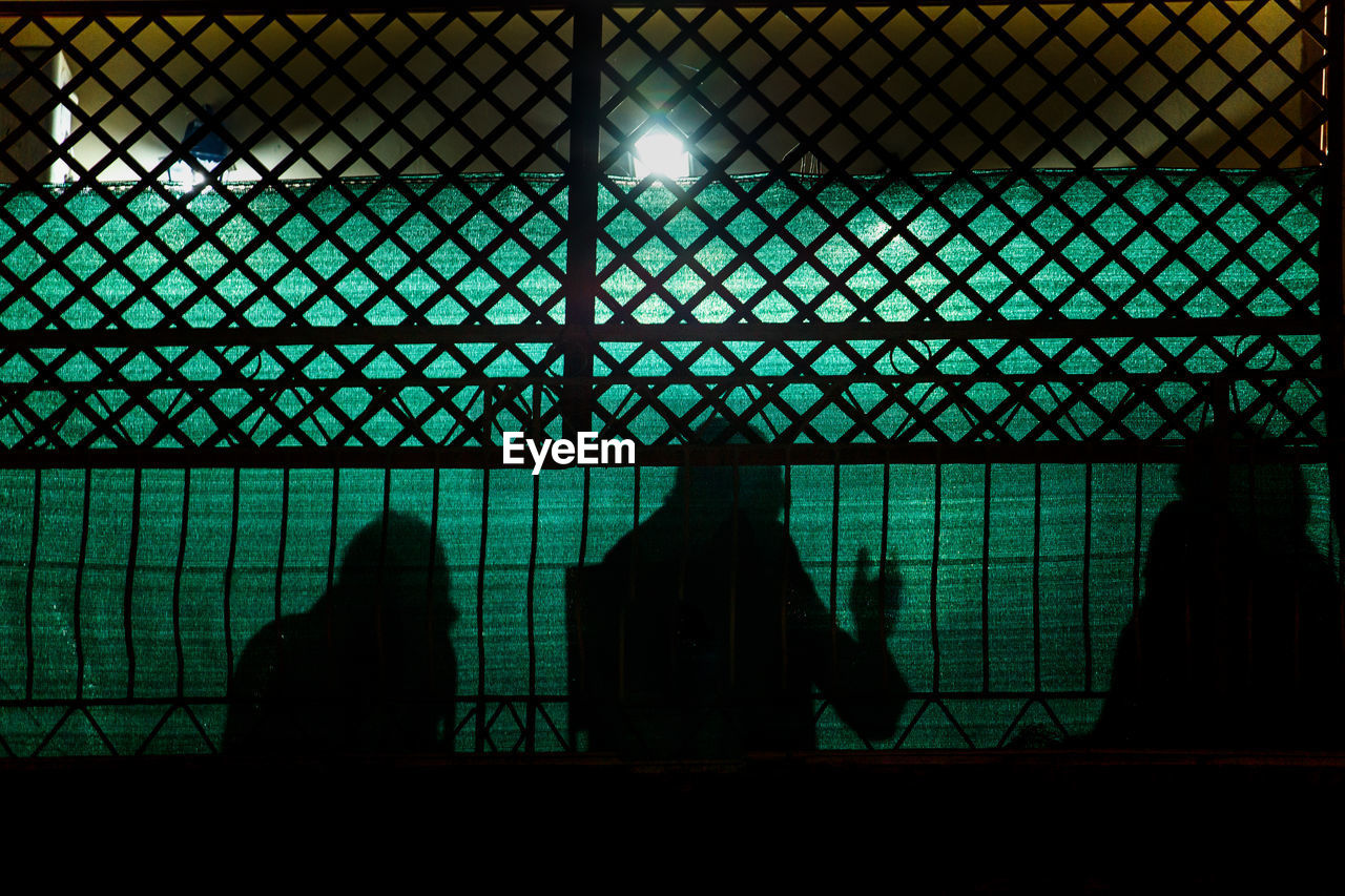 Shadow Of People Having Discussion Against Fence