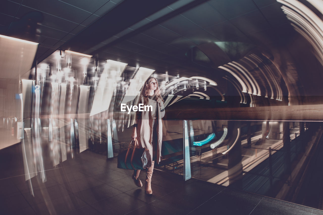 architecture, real people, indoors, one person, built structure, women, adult, illuminated, lifestyles, reflection, full length, glass - material, leisure activity, digital composite, standing, clothing, casual clothing, fashion, motion