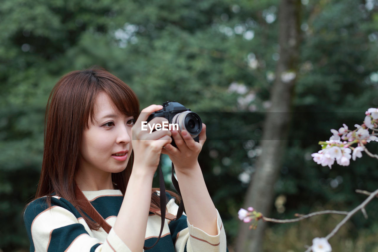Woman Photographing Plants With Digital Camera At Park