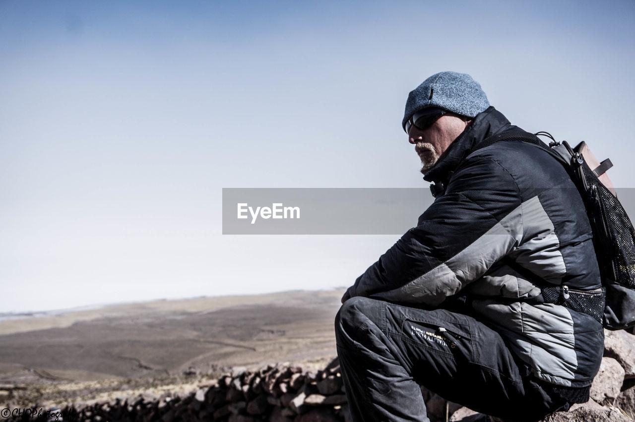 Man Looking Away Against Clear Sky