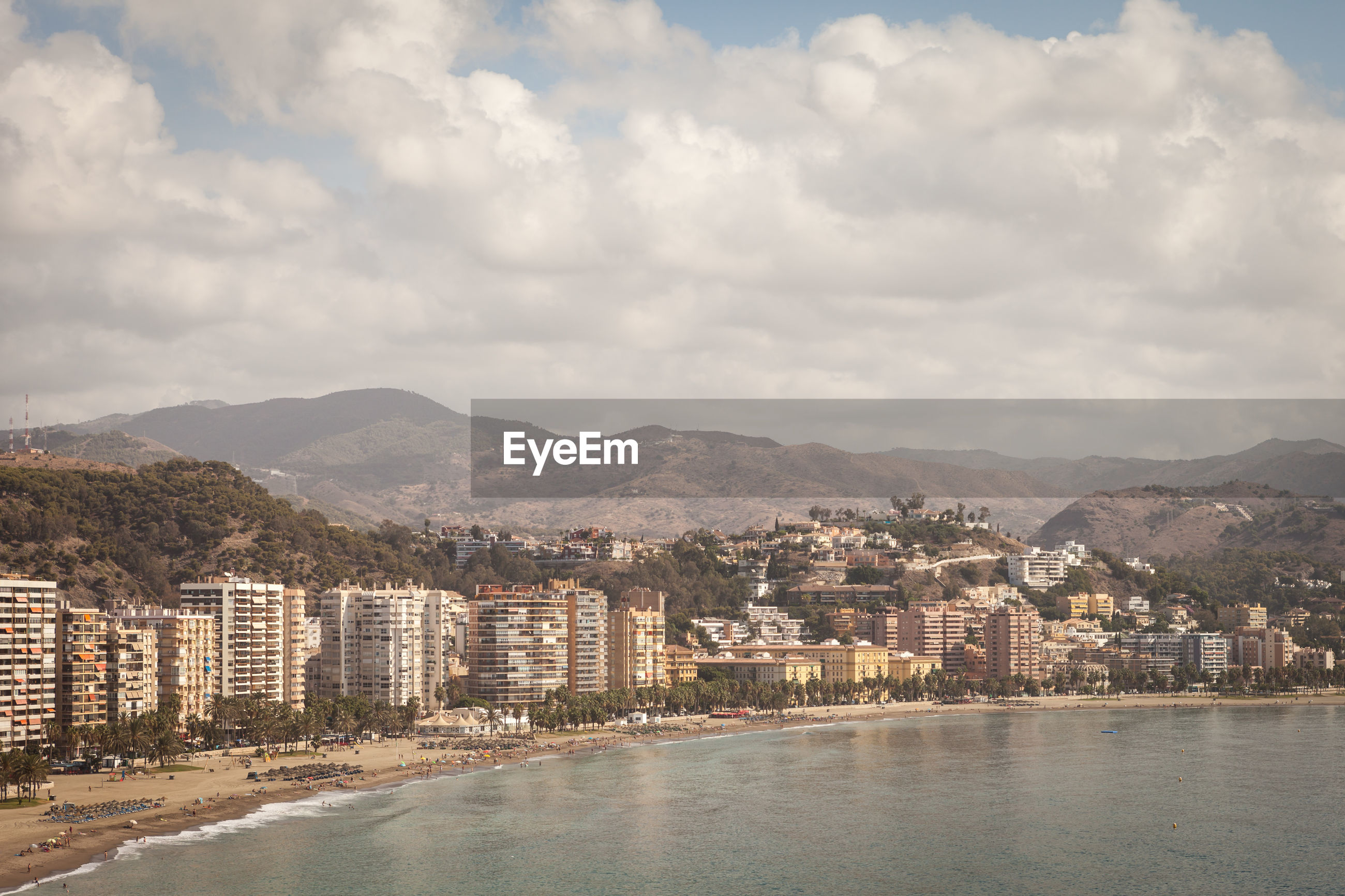 Scenic view of sea with town against cloudy sky