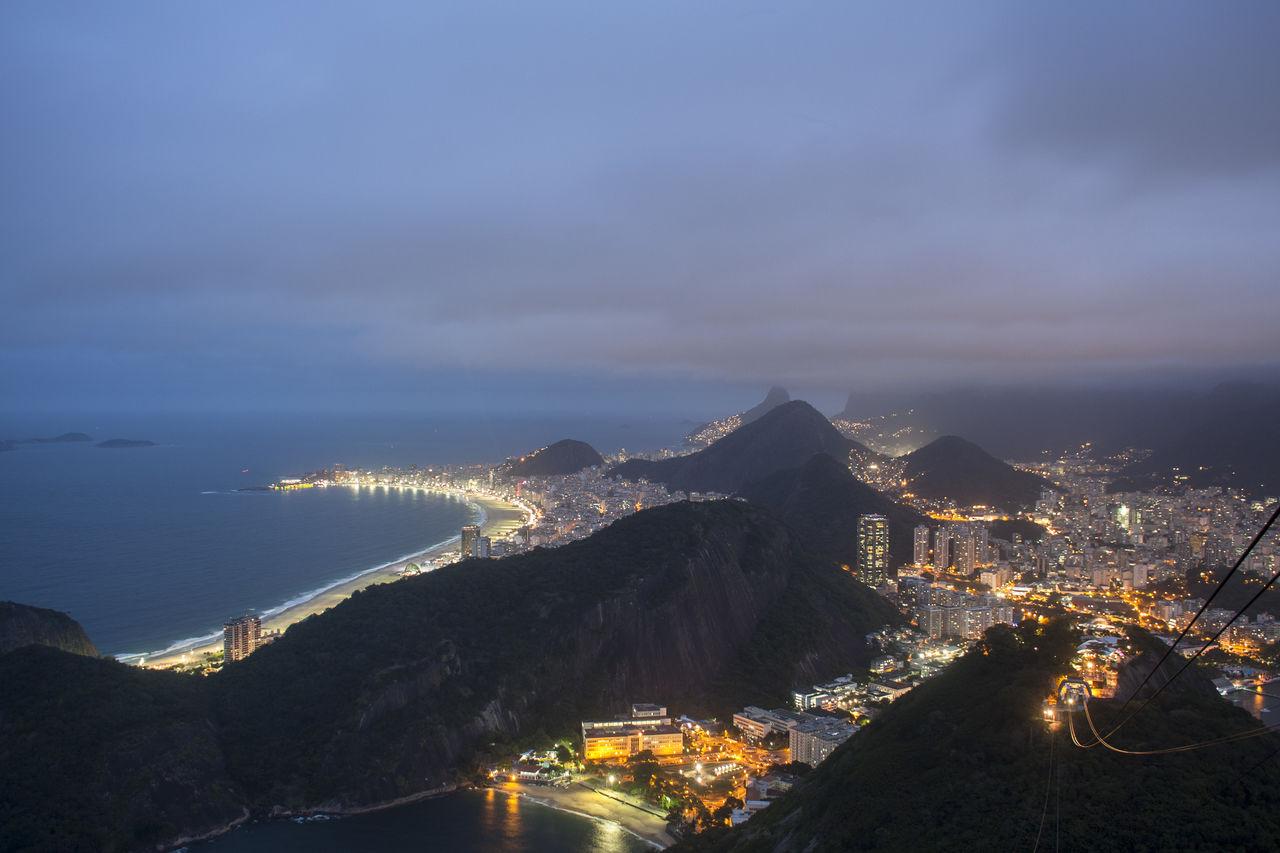 Illuminated Cityscape Against Sea At Night