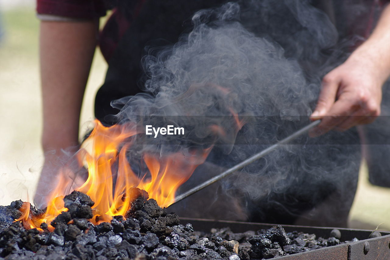 Midsection Of Man Burning Coal In Barbecue
