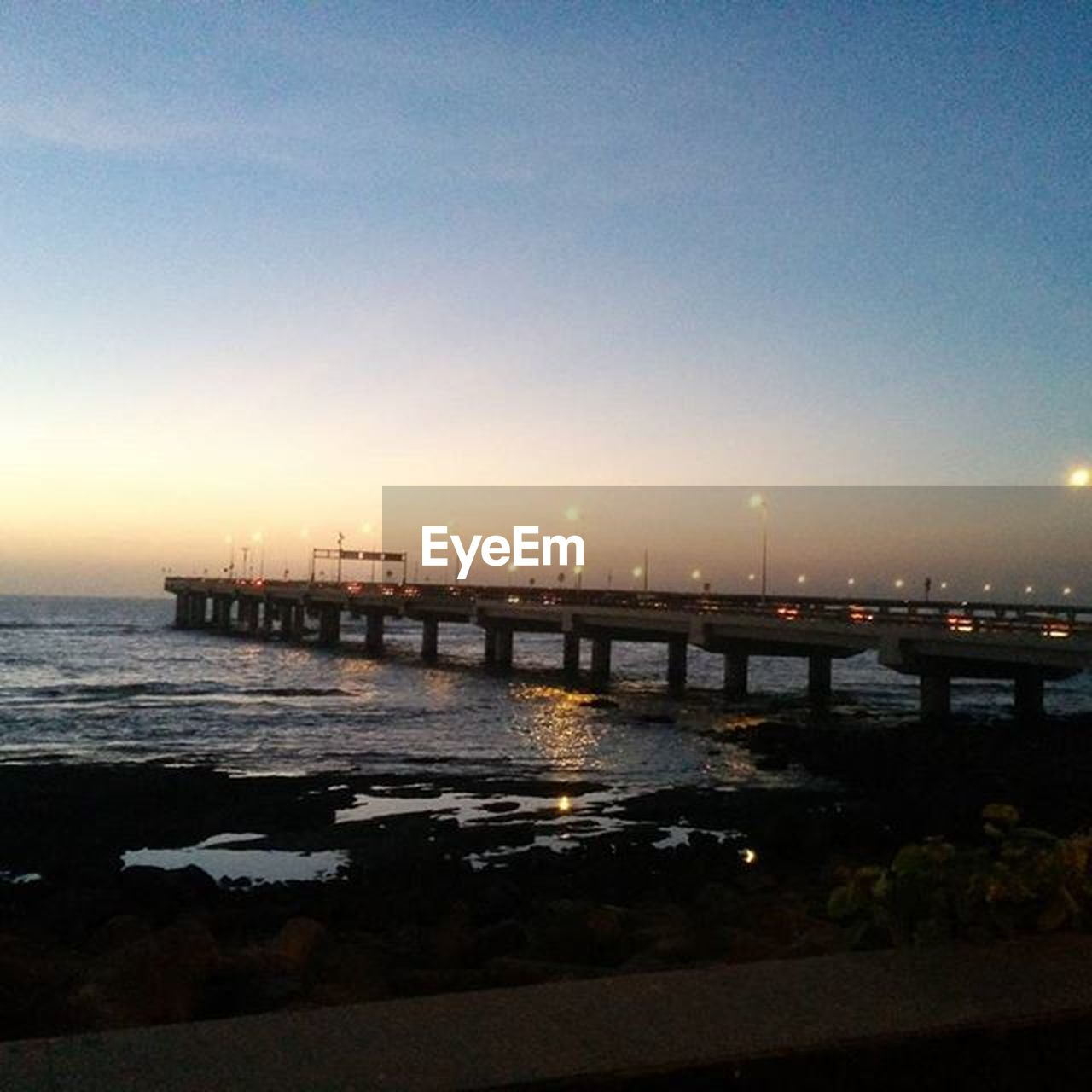 bridge - man made structure, sea, sunset, transportation, built structure, water, architecture, connection, no people, dusk, outdoors, sky, city, bridge, travel destinations, illuminated, night, nature, clear sky, nautical vessel, horizon over water, cityscape