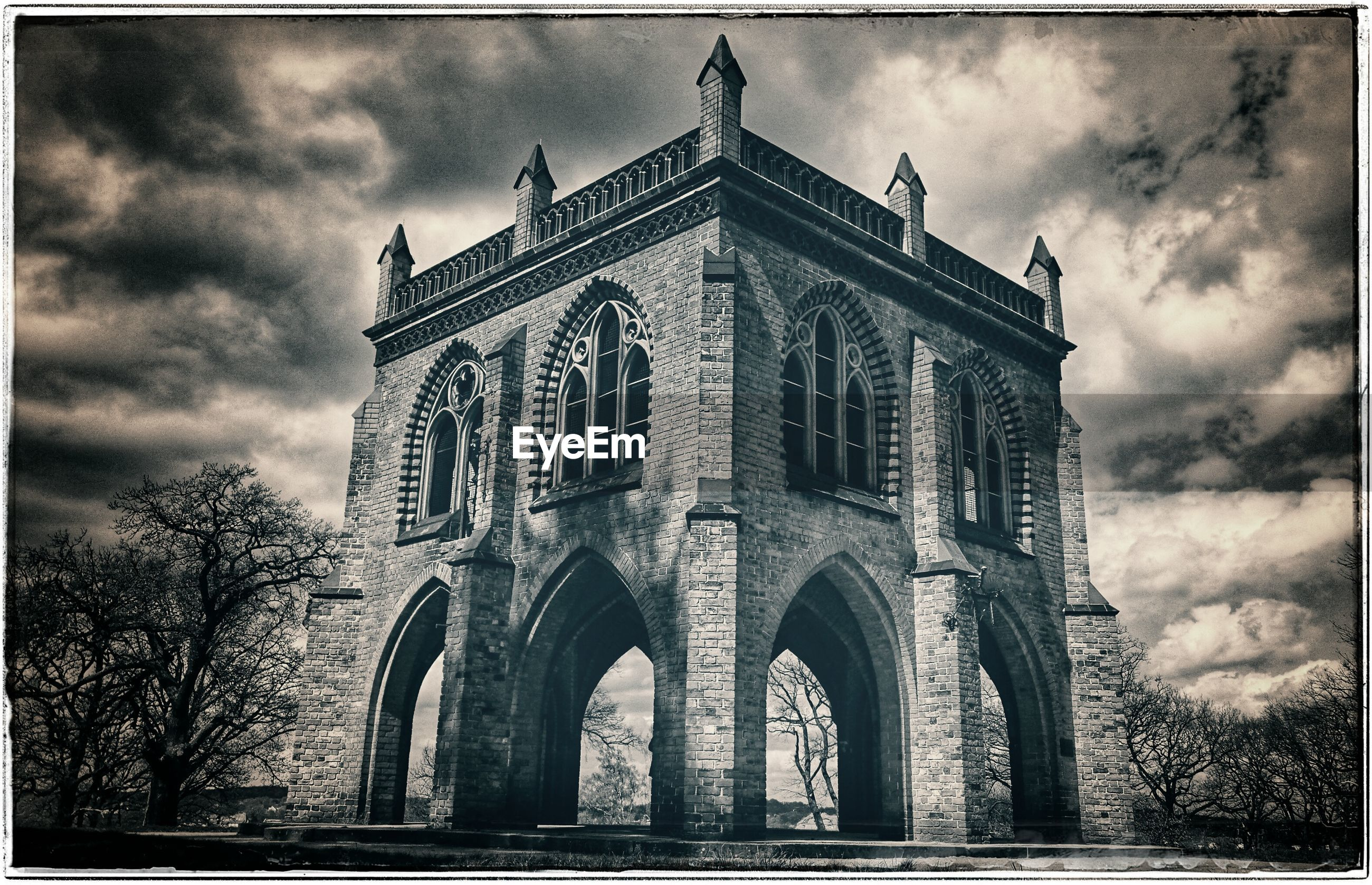 transfer print, architecture, sky, built structure, cloud - sky, low angle view, auto post production filter, cloudy, building exterior, arch, cloud, history, old, overcast, day, outdoors, tree, no people, facade, building