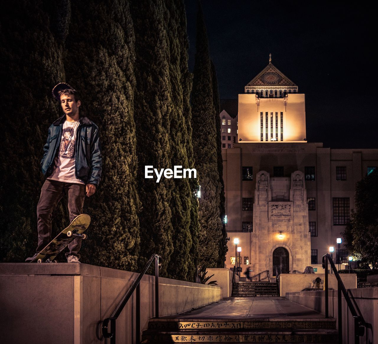 night, illuminated, casual clothing, tree, architecture, real people, one person, young adult, standing, leisure activity, built structure, young men, outdoors, lifestyles, building exterior, smiling, portrait, city, sky, nature, people
