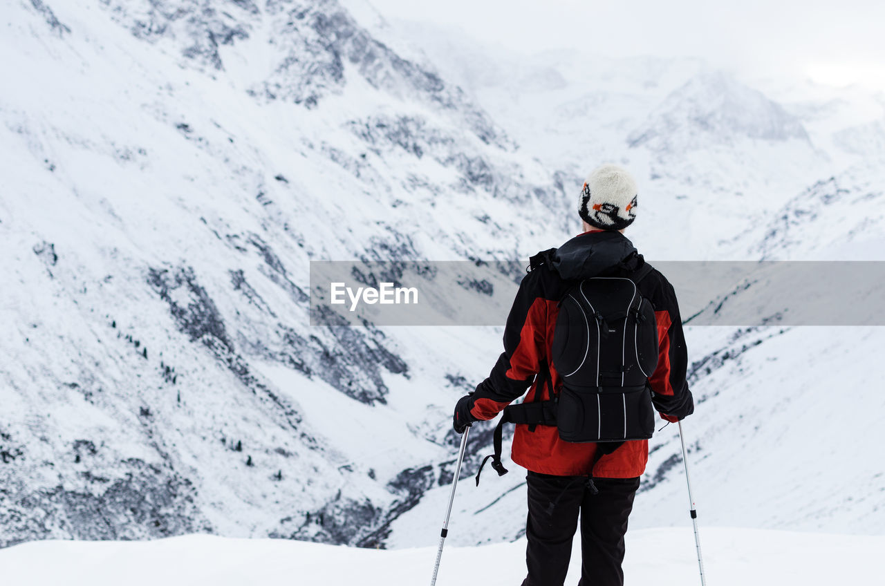 Rear View Of Man Skiing On Snow Covered Mountain