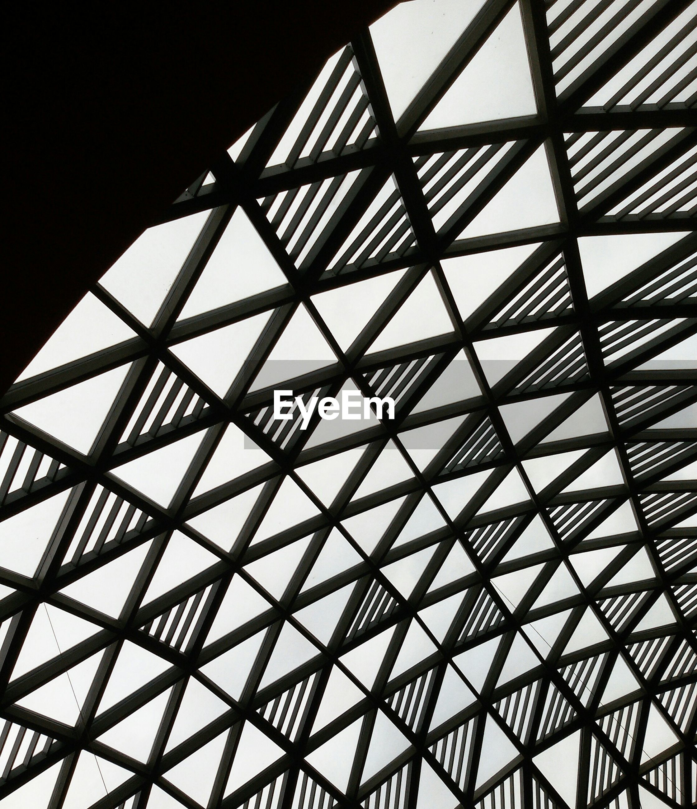 low angle view, architecture, built structure, pattern, ceiling, indoors, geometric shape, glass - material, architectural feature, design, full frame, backgrounds, modern, directly below, grid, skylight, no people, sky, day, metal
