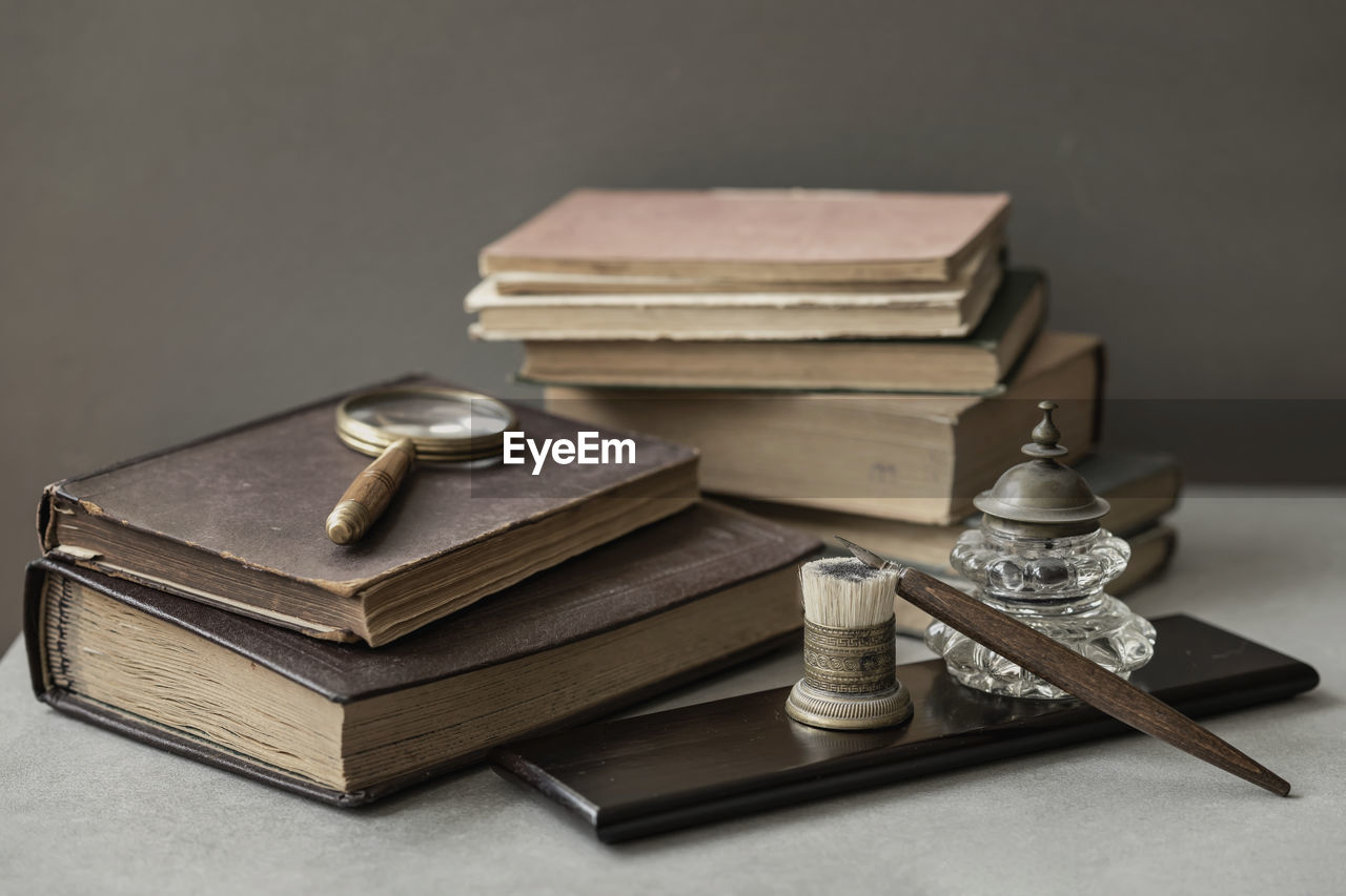 still life, stack, no people, indoors, table, large group of objects, book, publication, close-up, metal, studio shot, wood - material, antique, finance, old, selective focus, security, protection, business, hardcover book