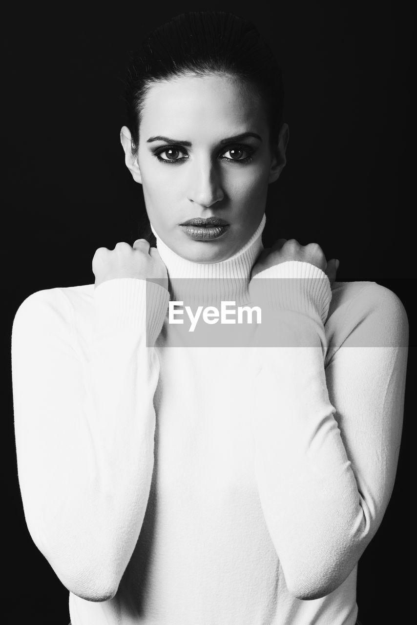 Portrait Of Woman Wearing Turtleneck Against Black Background