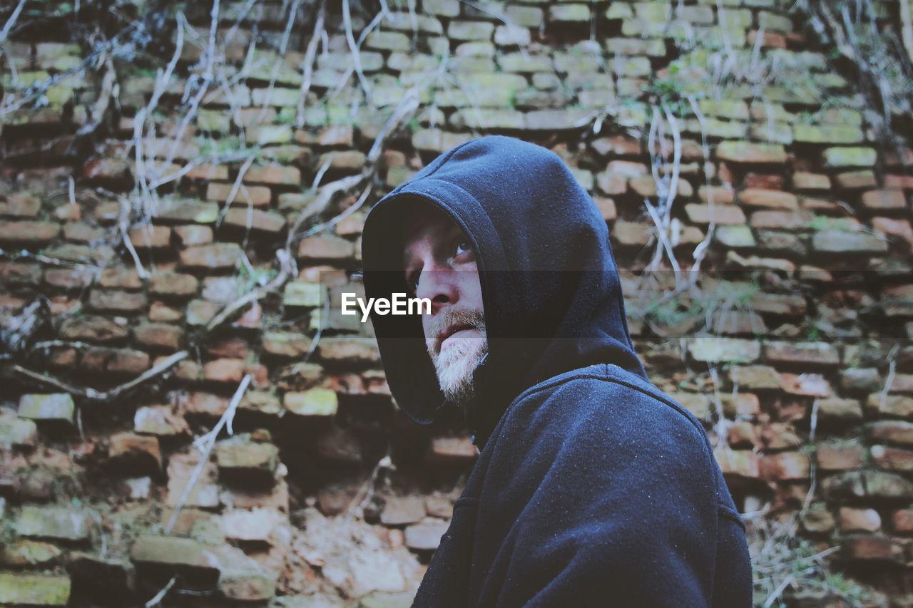 Man in hood- clothing standing against brick wall