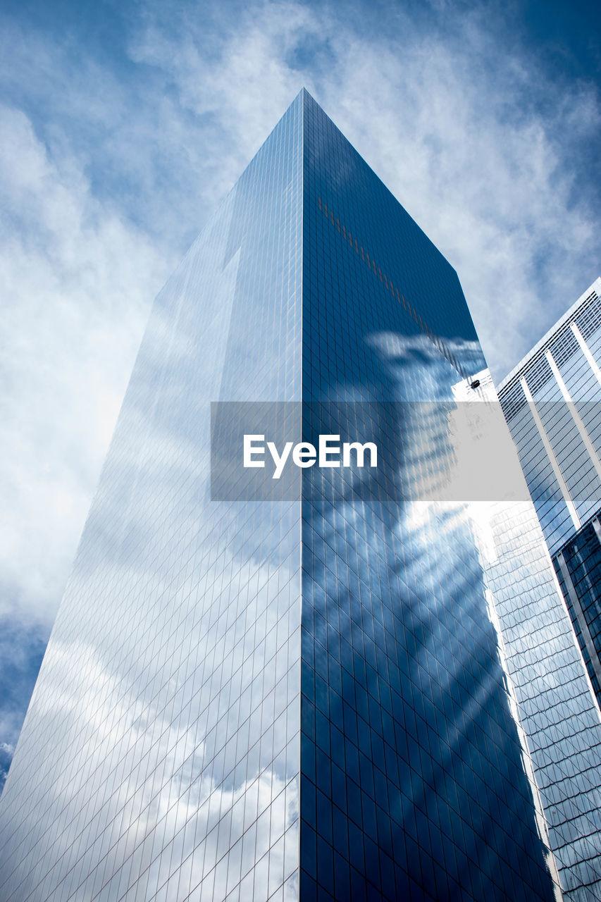 DIGITAL COMPOSITE IMAGE OF MODERN GLASS BUILDING AGAINST SKY