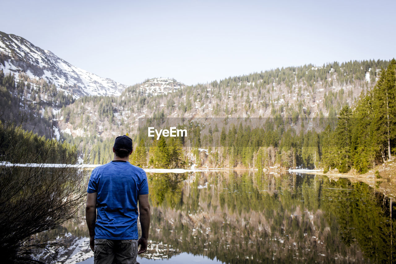 rear view, water, scenics - nature, tree, beauty in nature, plant, mountain, one person, nature, lake, real people, men, standing, non-urban scene, leisure activity, sky, day, lifestyles, vacations, outdoors, looking at view, flowing water