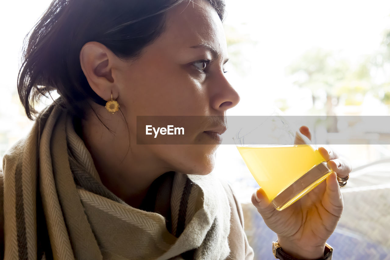 Close-Up Of Thoughtful Woman Having Drink In Glass