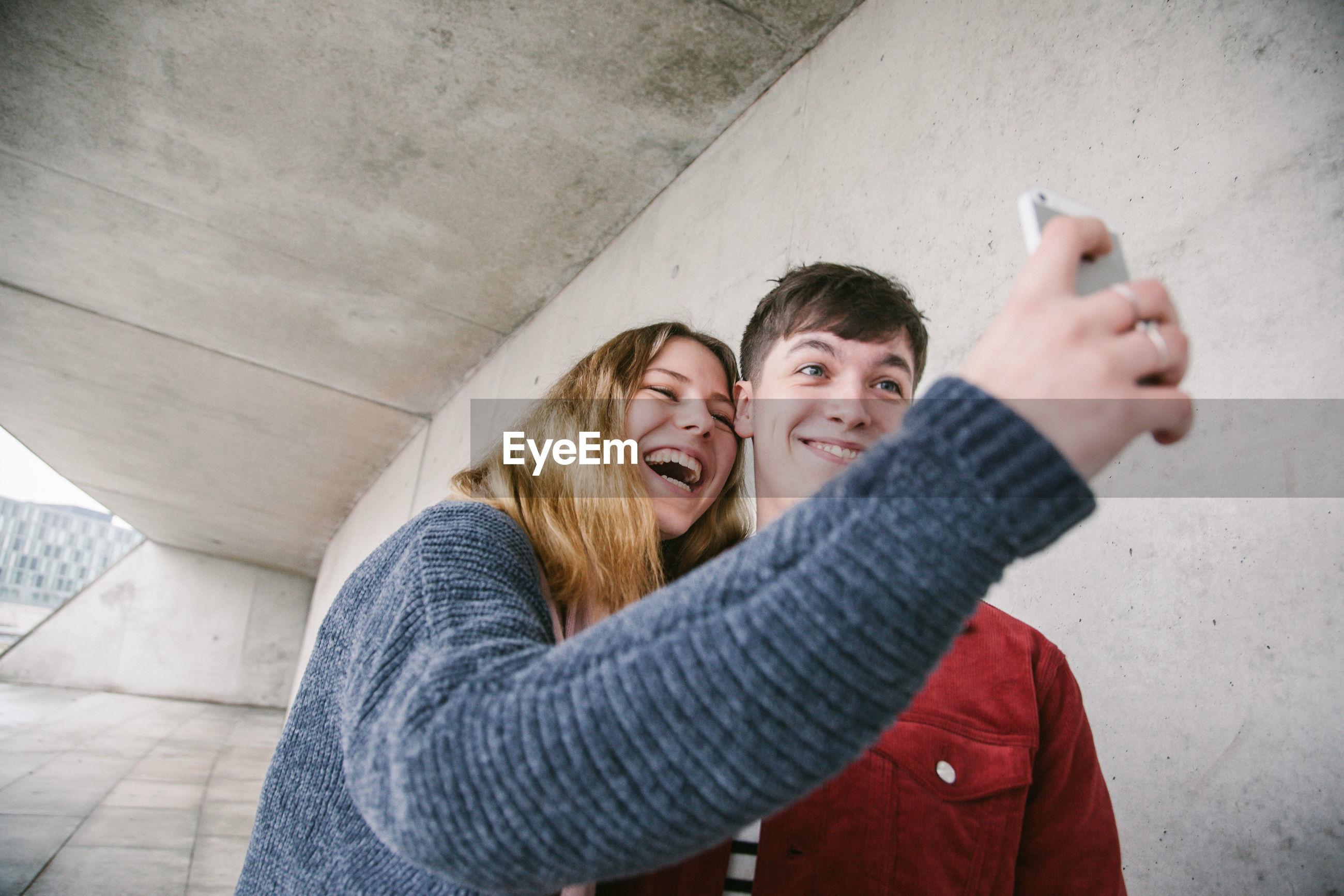 Happy friends taking selfie against wall