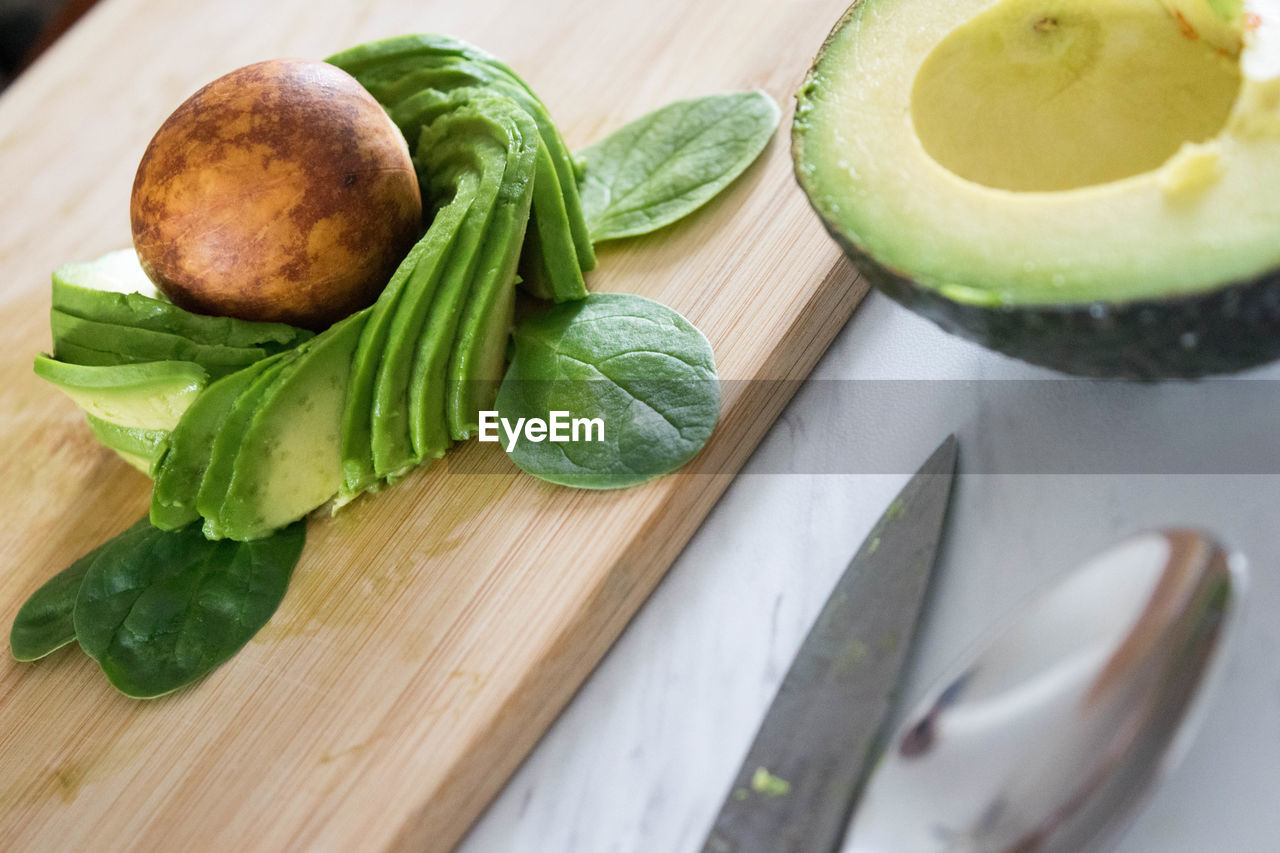 food and drink, food, freshness, indoors, cutting board, preparation, table, healthy eating, close-up, high angle view, green color, no people, preparing food, chopping board, wood - material, slice, leaf, day, ready-to-eat