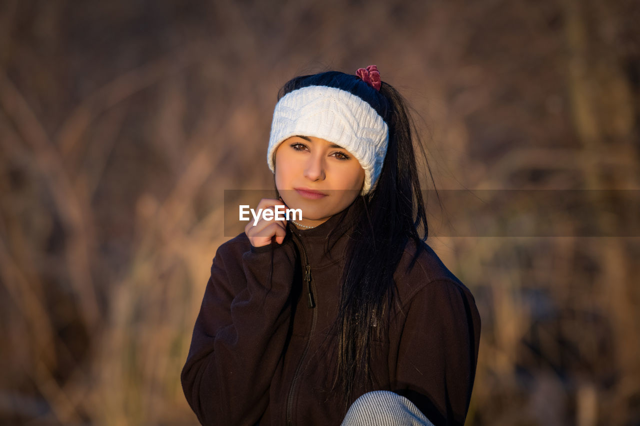 one person, focus on foreground, young adult, portrait, young women, front view, real people, lifestyles, clothing, leisure activity, beautiful woman, standing, looking at camera, beauty, hat, women, looking, long hair, hairstyle, hair, warm clothing, outdoors, contemplation