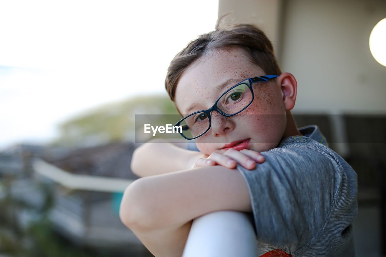 Side view portrait of boy leaning on railing at balcony