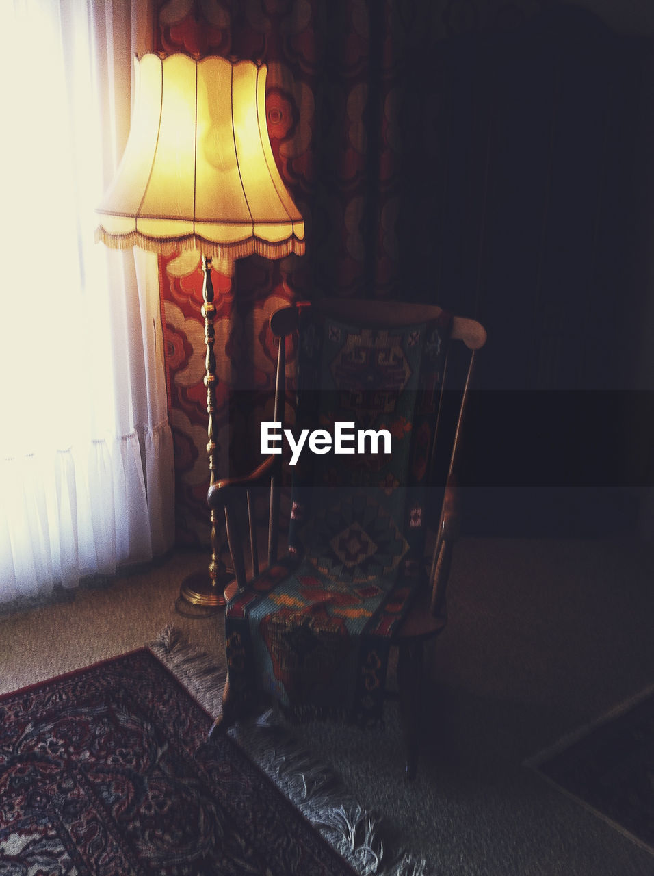 Empty rocking chair by lamp at home