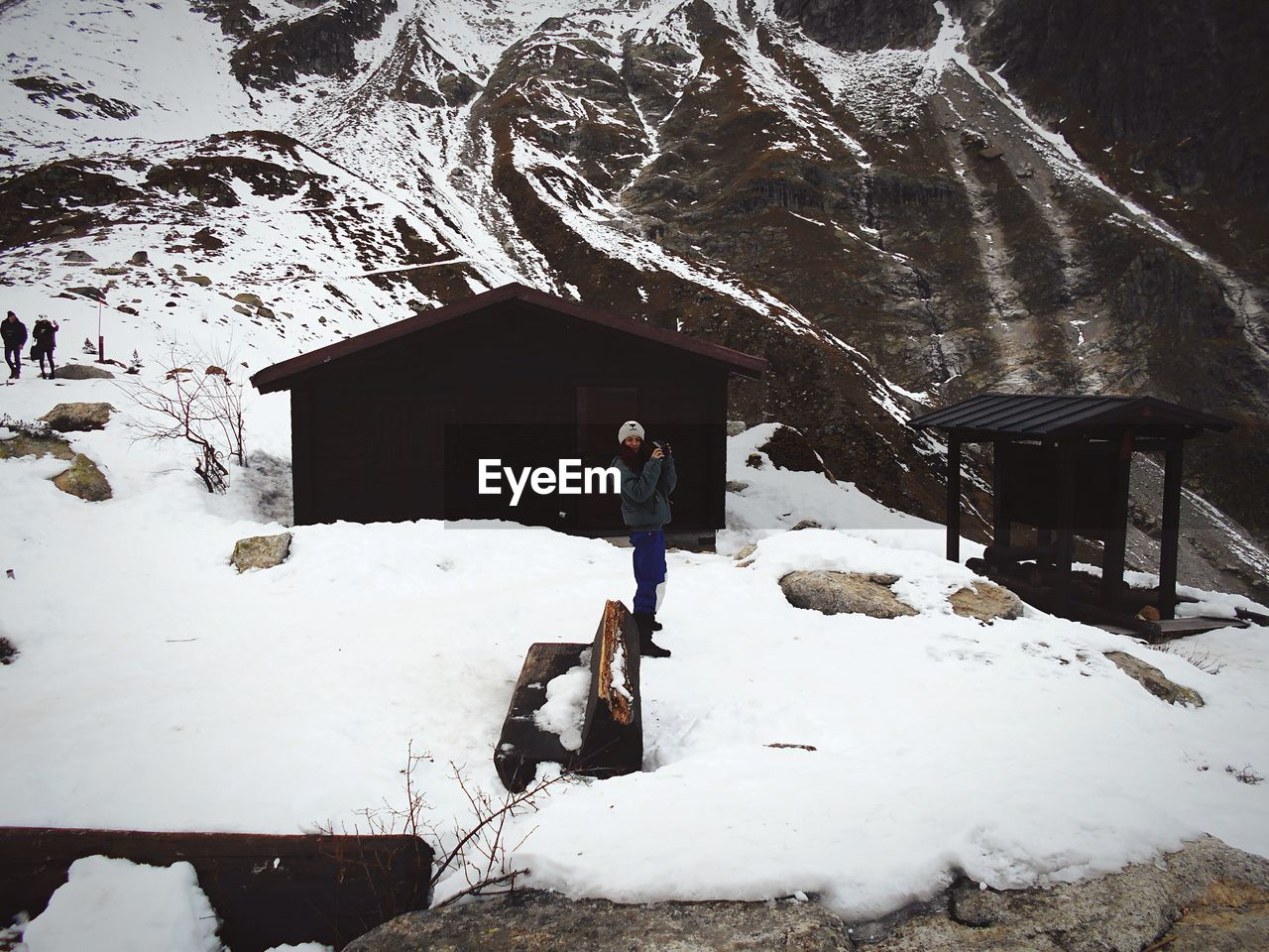 Full Length Of Woman Standing By Hut On Snowcapped Mountain