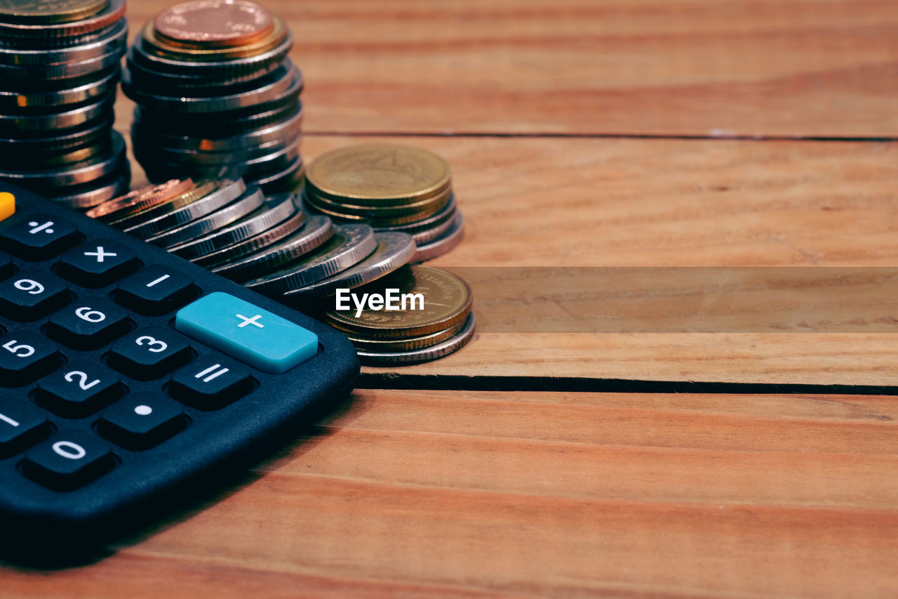 Close-up of calculator and coins on wooden table