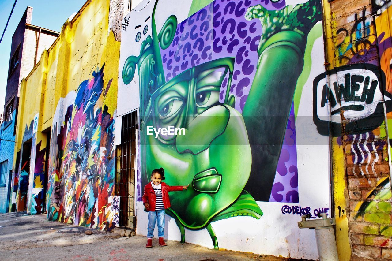 graffiti, art and craft, creativity, multi colored, street art, human representation, day, built structure, outdoors, architecture, artist, real people, one person, people