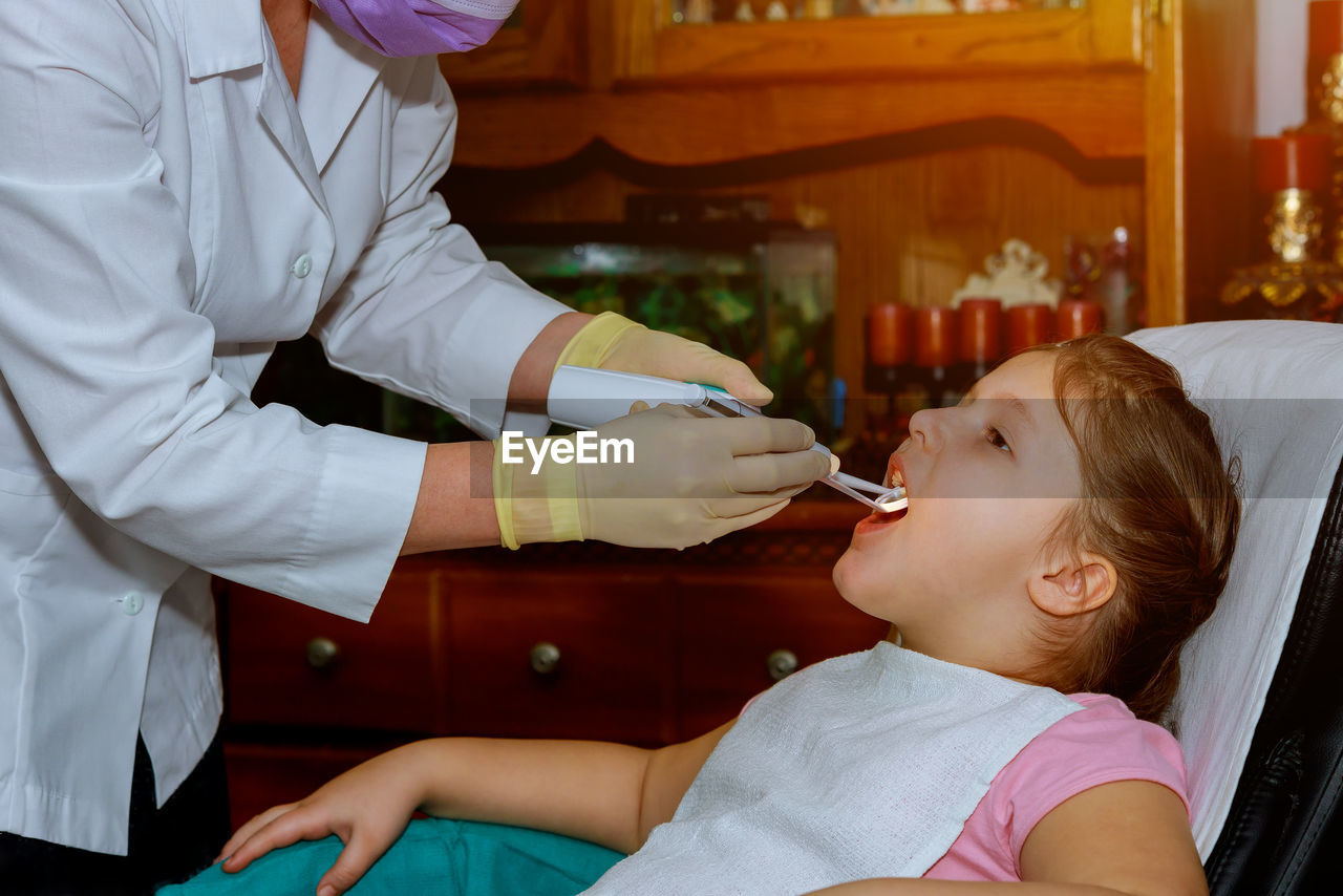 Midsection Of Dentist Examining Girl Teeth In Clinic