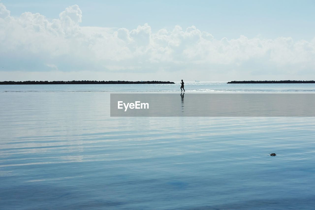 water, waterfront, sky, nature, day, beauty in nature, reflection, outdoors, sea, one person, leisure activity, tranquility, real people, men, scenics, paddleboarding, full length, swimming, people