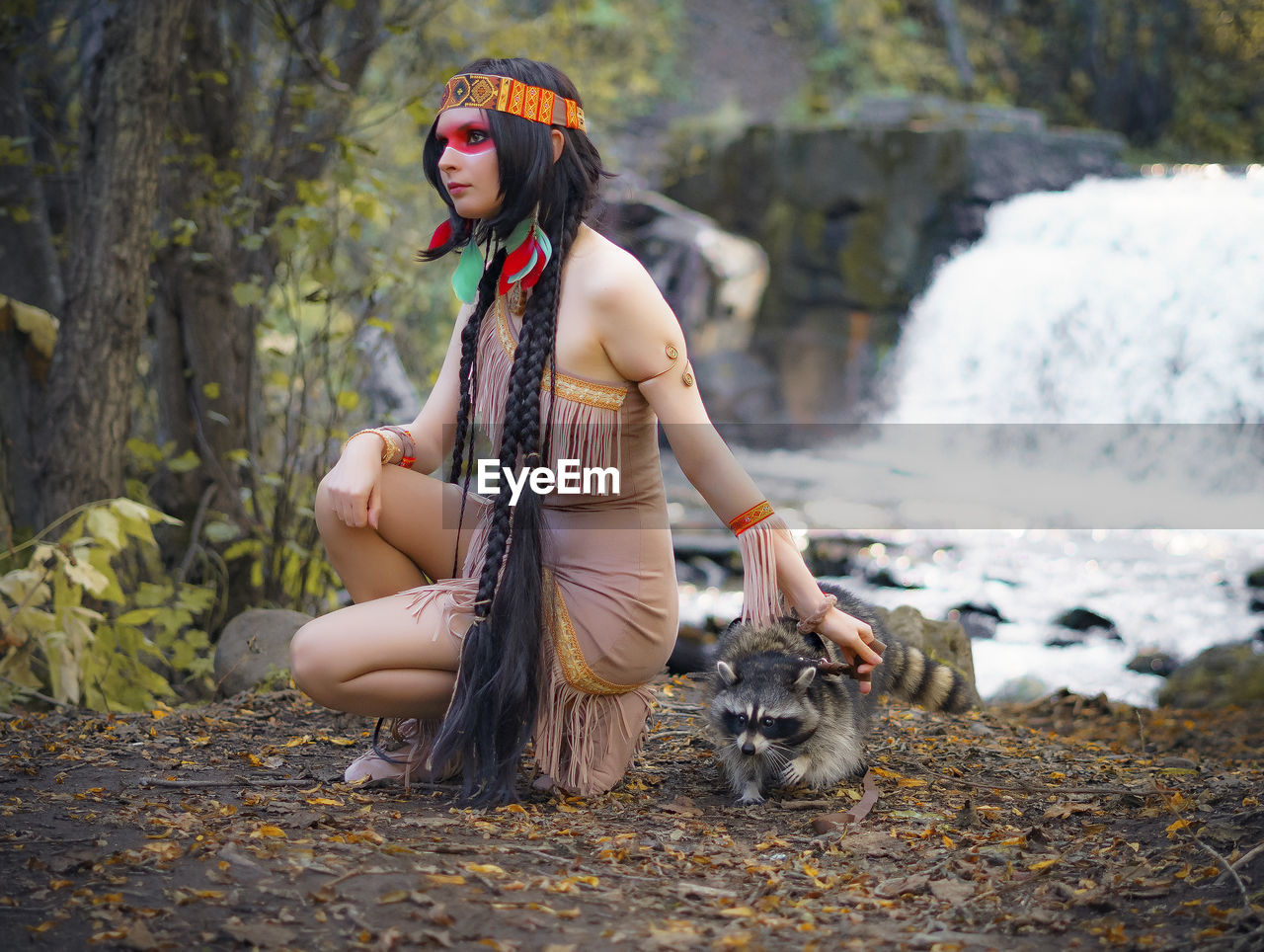 Young Woman In Traditional Clothing Looking Away While Crouching By Raccoon In Forest