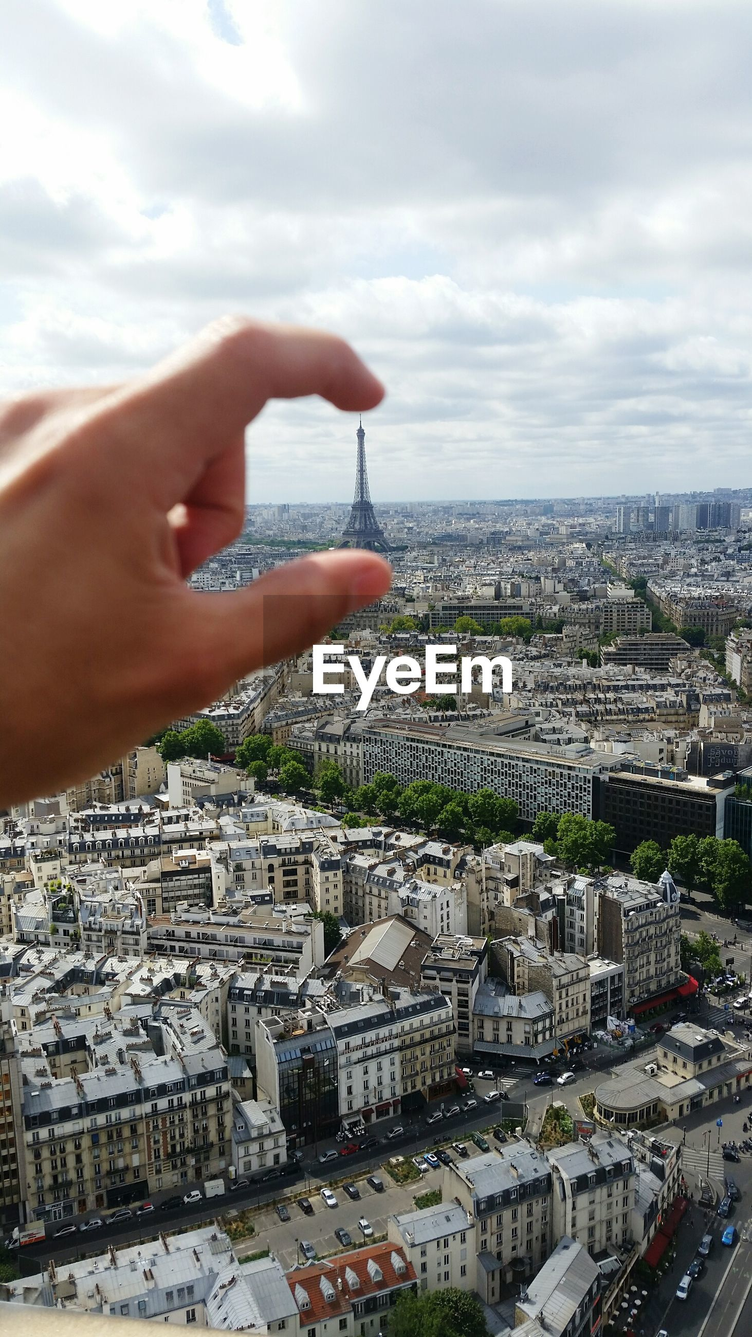 Optical illusion of cropped hand holding eiffel tower