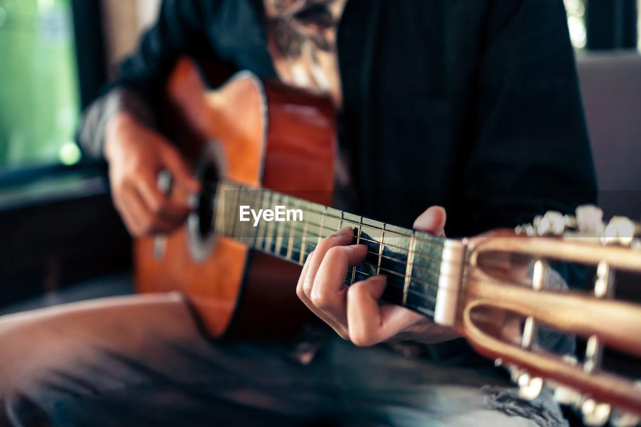 Close-up of man playing guitar indoors