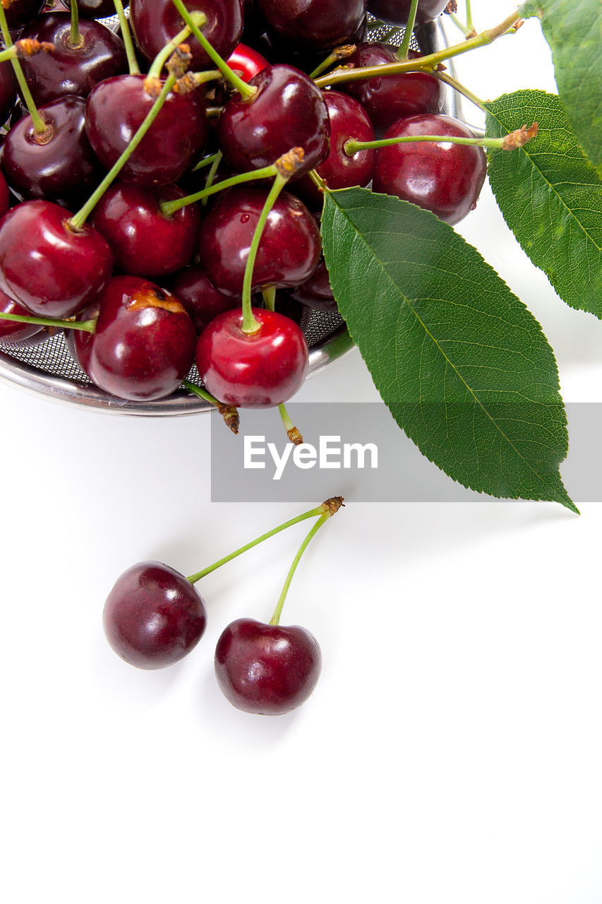 food, leaf, food and drink, plant part, healthy eating, freshness, fruit, red, wellbeing, close-up, no people, indoors, cherry, plant, still life, green color, nature, ripe, studio shot, white background, leaves