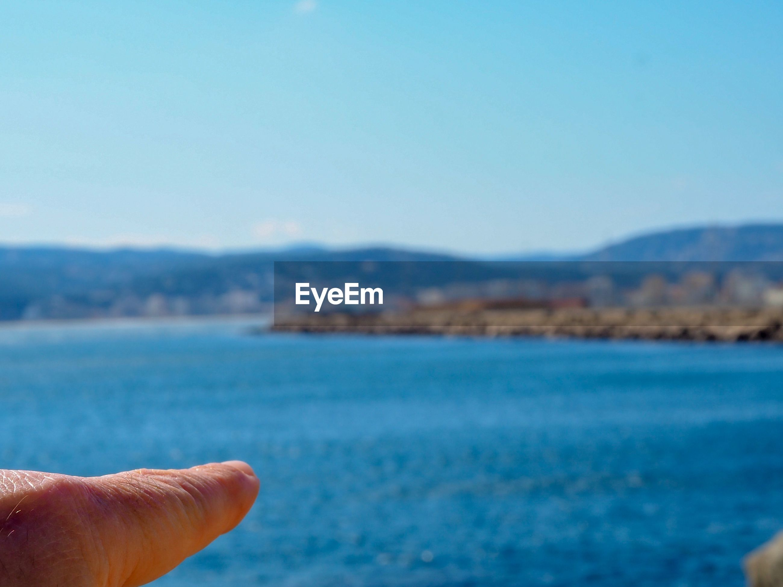 Cropped finger pointing at sea against sky