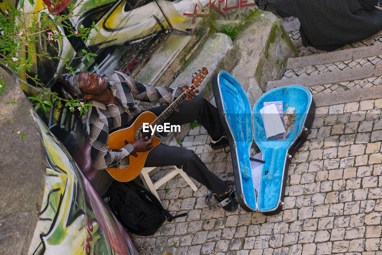 music, high angle view, musical instrument, day, outdoors, shoe, guitar, no people